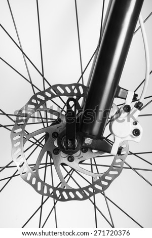 Disk brake of the bicycle. Part of Mountain Bike brake disc in close up. Front wheel of the mountain bicycle with the hydraulic disk brake. - stock photo