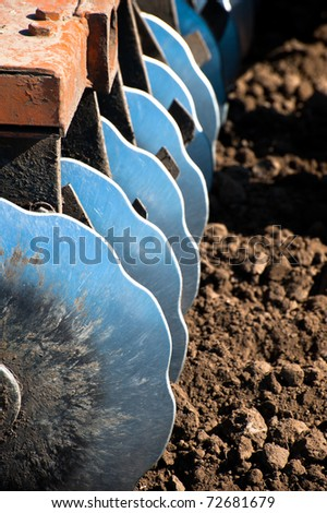 Disk harrow sitting in plowed soil - stock photo