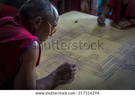 Diskit, Ladakh - August 20, 2015: View of buddhist monk working on mandala. Mandala is a spiritual and ritual symbol in Indian religions, representing the universe. - stock photo