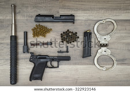 Dismantled gun pistol with new and used bullets, bat police and handcuffs on wooden background. - stock photo