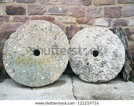 dismantled mill stones and rustic wall supported - stock photo