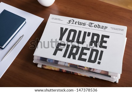 Dismissal notice writing on the front page of newspaper stack on business desk - stock photo