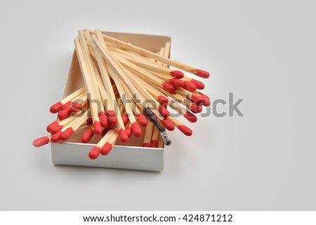 Disordered red head matches in a white opened box on white background