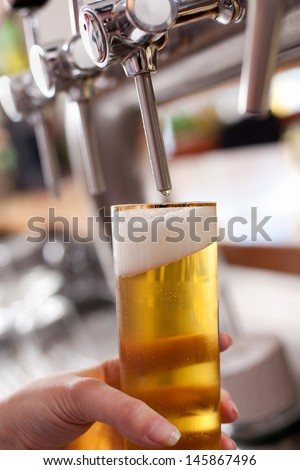 Dispensing draft beer into a pint glass at a bar or club from a metal spigot - stock photo