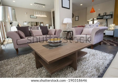 Display lounge area in large furniture show room with sofa and table - stock photo