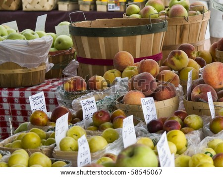 Display of fruits and vegetables at an outdoor farmers market with baskets of apples and peaches