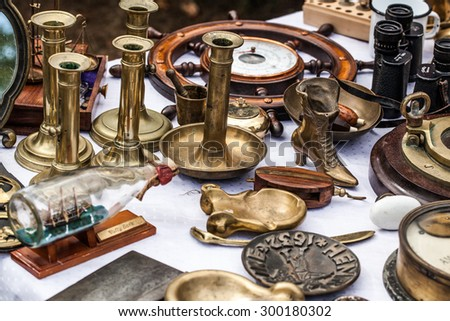 display of old brass candleholders,ashtrays,miniature boats on glass bottle and other brass objects for collection sold at flea market for antique collection