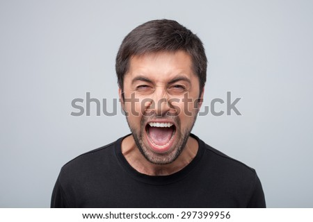 Displeased aggressive guy is looking at the camera with threatens. He is shouting with frustration and danger. Isolated on grey background - stock photo