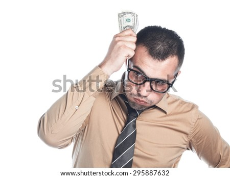 Displeased businessman count - holding money, isolated on white background. Employee young man with small profit. Bankruptcy concept, finacial crisis. - stock photo