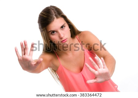 Displeased Hispanic young woman with stop or stay away gesturing - stock photo