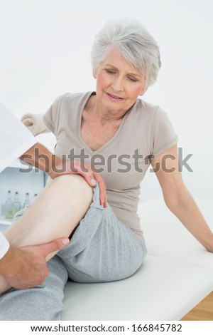 Displeased senior woman getting her leg examined at the medical office - stock photo