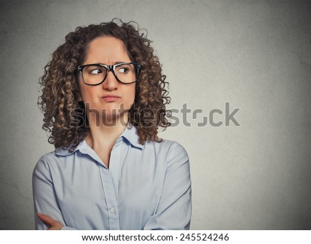 Displeased suspicious young woman with glasses looking sideways isolated on grey wall background. Negative face expression emotion perception