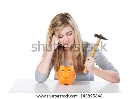 Displeased teenage girl with piggy bank and hammer against white background - stock photo