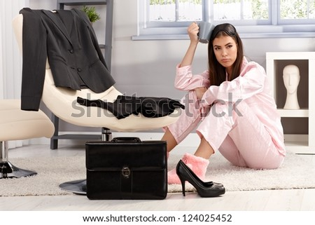Displeased tired young woman in pyjama getting ready for work, sitting on living room floor surrounded with business clothes and briefcase, having coffee. - stock photo