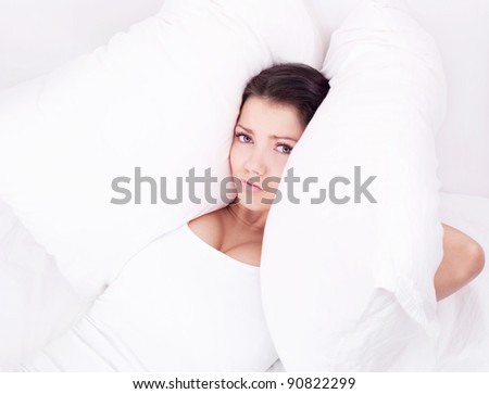 displeased  young brunette woman frowning and closing her ears with pillows, in bed at home