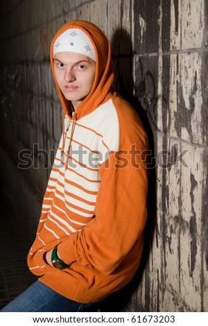 Displeased young punk slanging on the corner at night - stock photo