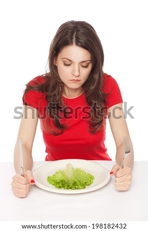 Displeased young woman eating green leaf lettuce, isolated on white - stock photo