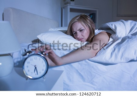 Displeased young woman in bed extending hand to alarm clock at home - stock photo