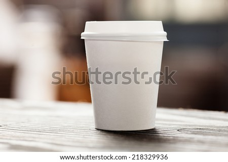 Disposable coffee cup on table - stock photo