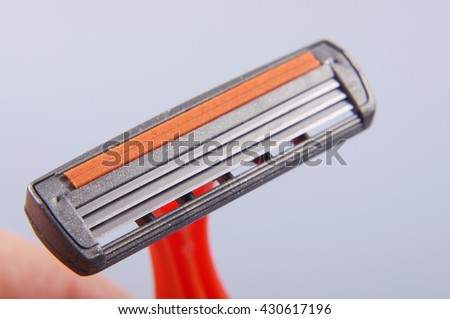 Disposable plastic shaver blade isolated on the gray background - stock photo