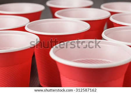 disposable red plastic cups on the wooden table - stock photo