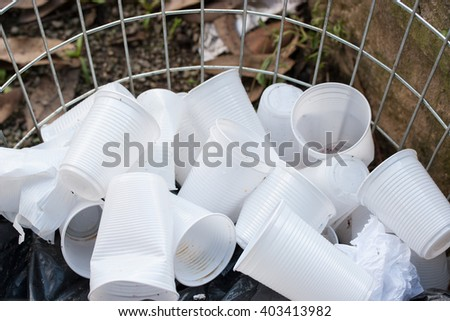 Disposable white plastic cups in open garbage container - stock photo