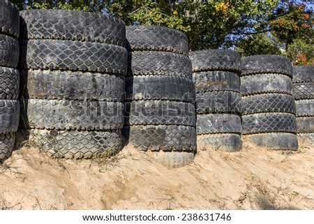 Disposal pile of old tires in the form of security fencing for spectators during the competition dangerous cars on a closed track cars - stock photo