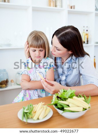 Dissatisfied blond girl eating vegetables with her mother in the kitchen