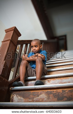 Dissatisfied child sitting on a damaged wooden stair case - stock photo