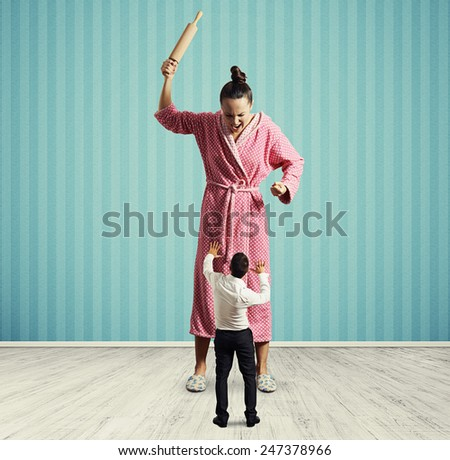 dissatisfied housewife with rolling pin screaming at small startled husband - stock photo