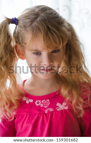 dissatisfied little lady posing by the window - stock photo