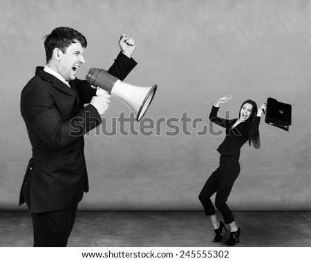 dissatisfied man screaming at small scared woman over dark background - stock photo