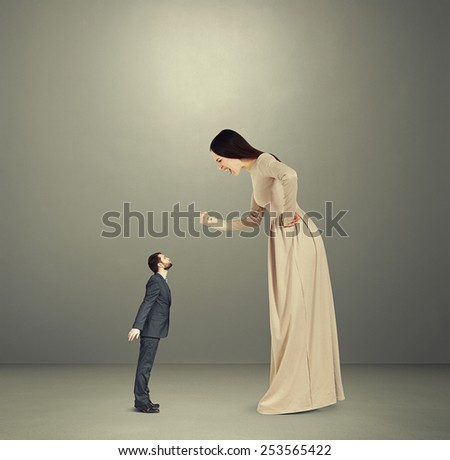 dissatisfied young woman screaming and showing fist to small kissing man. concept photo in empty grey room - stock photo