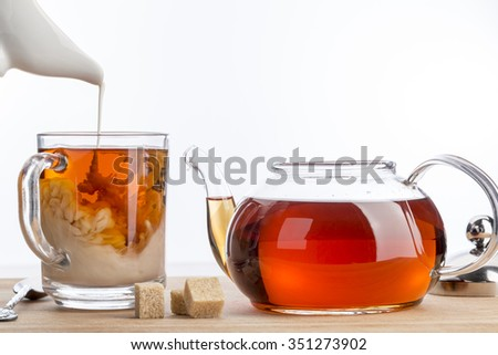 Dissolve milk in a cup of black tea. Transparent teapot and cup with three cubes of brown sugar on white background - stock photo