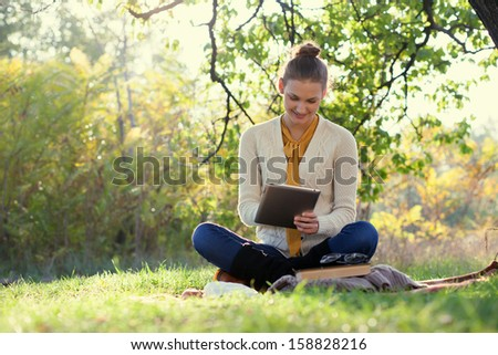 Distance education. Sitting woman using tablet during autumn fun outdoors - stock photo