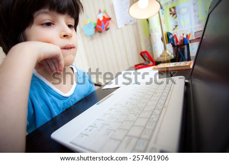 distance learning, a boy with computer in the interior - stock photo