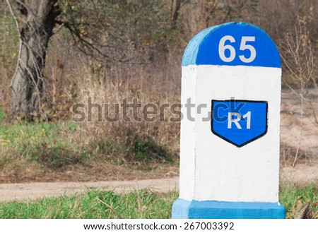 Distance sign indicator on the road with forest background - stock photo