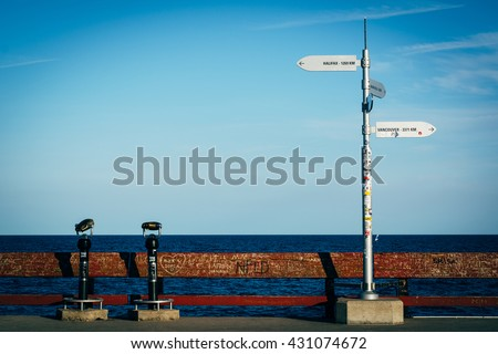 Distance signs on the fishing pier at Centre Island, in Toronto, Ontario. - stock photo