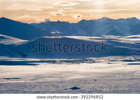 Distant caribou tracks lead toward the Philip Smith Mountains in the Arctic National Wildlife Refuge in Alaska - stock photo