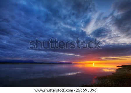 Distant cliffs sunset with intense dark clouds over a lake - stock photo