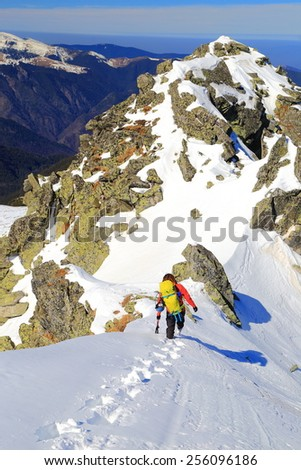 Distant climber approaching the summit on snow covered ridge - stock photo