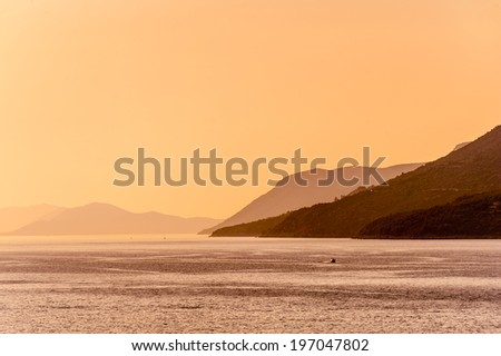 Distant hills in morning mist across the sea - stock photo