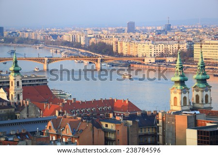 Distant Margaret bridge across Danube river and sunny rooftops, Budapest, Hungary - stock photo