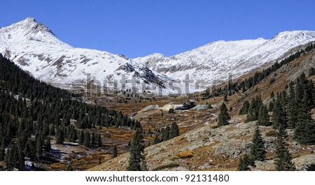 Distant mine in winter Colorado mountain valley - stock photo