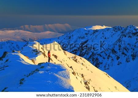 Distant mountaineer admiring the setting sun on a snowy mountain - stock photo