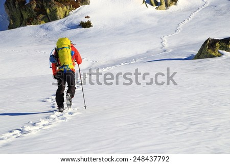 Distant mountaineer on white snow field at the base of the mountain - stock photo