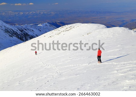 Distant mountaineers walking on the snow covered mountain slope - stock photo
