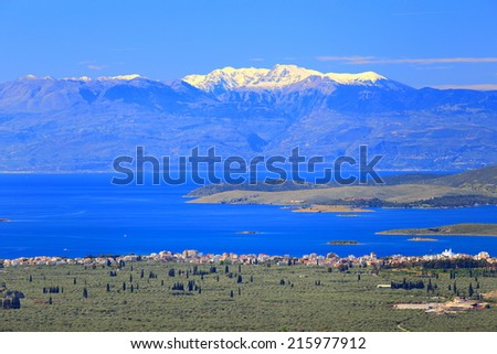 Distant mountains with snow on top seen across the Gulf of Corinth, Greece - stock photo