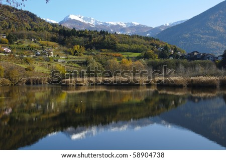 Distant peaks reflecting in the still waters of a lake during a sunny Autumn day - stock photo
