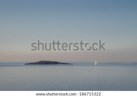 Distant sailboat and an island - stock photo